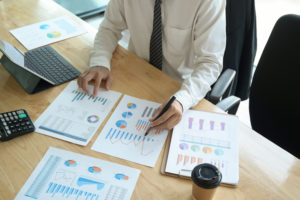 Mann schaut auf Zettel mit Qualitätskosten
